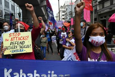 "Following the anti-communist raids, a member of women's group Gabriela holds a placard that reads ""Stop the Attacks!"" during a march towards the presidential palace on International Women's Day in Manila"
