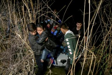 A group of undocumented migrants from Honduras and Guatemala get off a Mexican trafficker's boat on the US side of the border near Roma, Texas, on March 28 2021