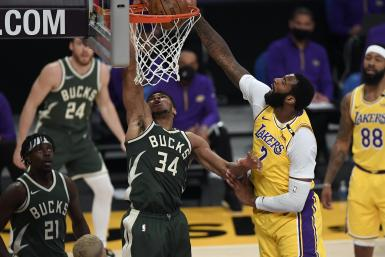 Giannis Antetokounmpo #34 of the Milwaukee Bucks scores a basket against Andre Drummond #2 of the Los Angeles Lakers