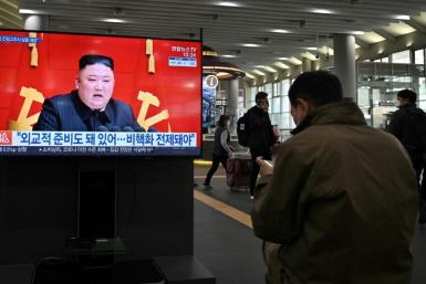 The United States held three-way talks with South Korea and Japan on how to handle North Korea, whose leader Kim Jong-Un is seen on a television screen in Seoul in March 2021