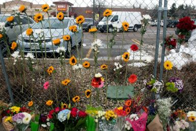 Flowers hang from the perimeter fence outside a King Soopers grocery store in Boulder, Colorado on March 23, 2021, one day after a mass shooting left ten dead, including a Boulder police officer