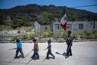 Children carry replica weapons through the Mexican village of Ayahualtempa before taking part in training in defense against drug traffickers