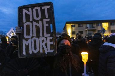 Demonstrators hold candles and signs ahead of an evening curfew in front of the Brooklyn Central Police Station outside Minneapolis, near where a policewoman shot dead Daunte Wright