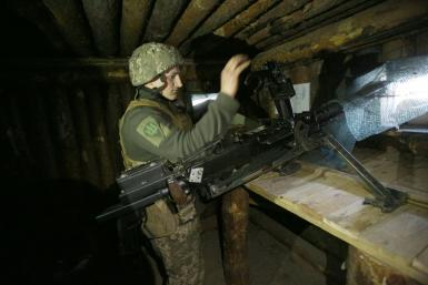 A Ukrainian soldier loads a heavy machine gun at a position on the frontline