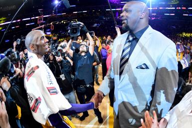 Kobe Bryant #24 of the Los Angeles Lakers talks with former teammate Shaquille O'Neal after scoring 60 points in his final NBA game at Staples Center on April 13, 2016 in Los Angeles, California.