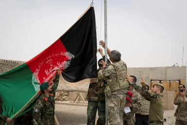 US troops and Afghan National Army (ANA) soldiers raise Afghanistan's national flag during a handover ceremony at Camp Antonik in Helmand province