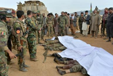 Afghan security forces gather around the bodies of Taliban militants in Nangarhar province in February 2021 -- the Taliban have declared a three-day Eid ceasefire