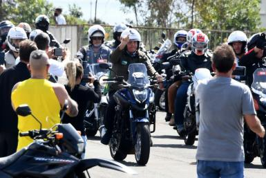 Brazil President Jair Bolsonaro (center) leads a motorcycle rally by supporters around the capital Brasilia to show support for the far right leader