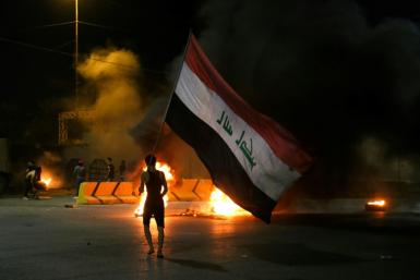 Iraqi protesters burn tyres in front of the Karbala governorate headquarters in the central city of Karbala on May 9, 2021 following the reported killing of prominent anti-government activist