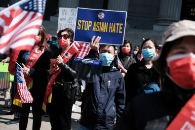 People participate in a protest to demand an end to anti-Asian violence