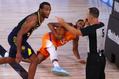 Referee Kane Fitzgerald #5 calls a foul as T.J. Warren #1 of the Indiana Pacers and Mikal Bridges #25 of the Phoenix Suns