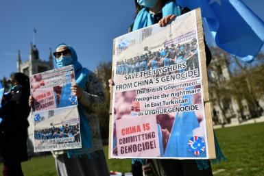 Members of the Uyghur community hold placards as they demonstrate to call on the British parliament to vote to recognise alleged persecution of China's Muslim minority Uyghur people as genocide and crimes against humanity in London on April 22, 2021