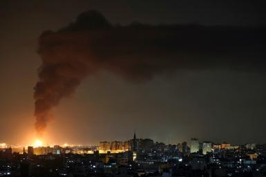 A huge column of smoke seen from Gaza city billows from an oil facility in the southern Israeli city of Ashkelon, on May 11, 2021, after rockets were fired by the Palestinian Hamas movement from the Gaza Strip towards Israel.