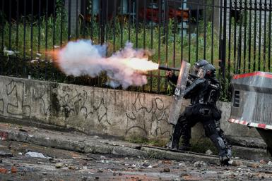 A riot police officer fires tear gas at demonstrators in Colombia, where anti-government protests have turned deadly