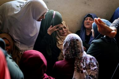 The mother of Palestinian Hussein Hamad, 11, is comforted by mourners after he was killed in an Israeli air strike in the northern Gaza Strip