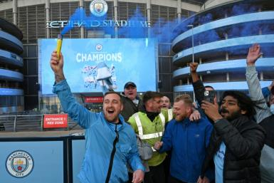 Blue moon rising: Manchester City fans celebrate clincning the Premier League title for the fifth time in nine years