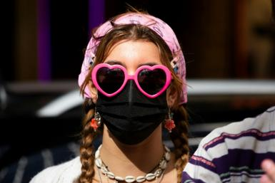 A woman wearing a face mask attends the Broadway United for Justice protest as workers commemorate May Day in New York