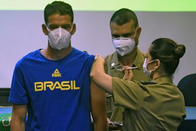 Brazilian bow and arrow athlete Marcus Vinicius D'Almeida is inoculated with a Covid-19 vaccine as part of a project organized by the Brazilian federal government to vaccinate Brazilian citizens accredited to the Tokyo Olympic Games amid the COVID-19 pand