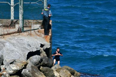 Migrants try to enter either by scaling the tall barrier fence or swimming