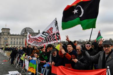 "Protesters hold a banner reading ""Stop war in Libya, Haftar and mercenaries"" during a protest in front of the Reichstag building during the Peace summit on Libya at the Chancellery in Berlin on January 19, 2020"
