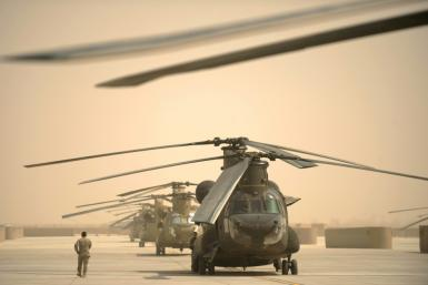 A US airman walks past a row of Chinook helicopters at Kandahar airbase in southern Afghanistan, which has now been turned over to the Afghan military as US forces withdraw from the country