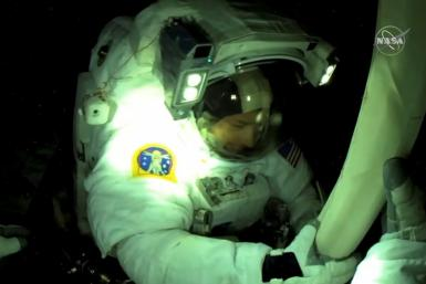 This NASA TV frame grab captured on June 20, 2021 shows US astronaut Shane Kimbrough seen from French astronaut Thomas Pesquet's helmet camera as the two installed a solar panel array on the International Space Station