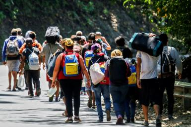 Venezuelan migrants walk along a highway in Cucuta, Colombia, on the border with Venezuela, on February 2, 2021, amid the COVID-19 pandemic