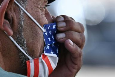 A man adjusts his American flag face mask on a street in Hollywood, California