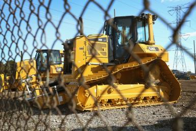 Caterpillar reported higher earnings but said customers in the oil and mining industries were holding off on major new investment