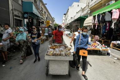 People walk along an alley in Tunisia's capital Tunis on July 28, 2021