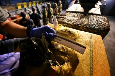 An official in Colombia inspects packages with cocaine on a seized submarine in the city of in Buenaventura on March 20, 2021