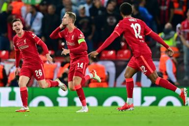 Jordan Henderson (C) celebrates with teammates after scoring his team's third goal during the UEFA Champions League 1st round Group B football match between Liverpool and AC Milan at Anfield in Liverpool, north west England on September 15, 2021.