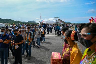Domestic tourists disembark from a Malaysia Airlines plane after landing in Langkawi