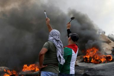 Palestinian protesters hold up spoons as they confront Israeli security forces in the West Bank village of Beita, on September 10, 2021