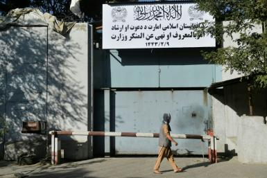 Workers put up a sign for the notorious Ministry for the Promotion of Virtue and Prevention of Vice at the old Women's Affairs building in Kabul