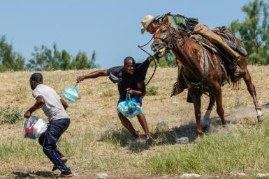 A United States Border Patrol agent on horseback tries to stop a Haitian migrant from entering an encampment on the banks of the Rio Grande near Del Rio, Texas.