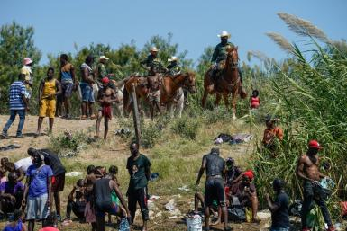 United States Border Patrol agents on horseback look on as Haitian migrants sit on the banks of the Rio Grande near Del Rio, Texas.
