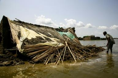 A South Sudanese refugee inspects a house damaged in floods in Al-Qanaa village in Sudan's southern White Nile state