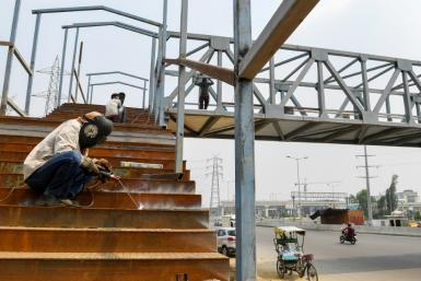 Workers build a bridge in Ghaziabad, India. The Asian Development Bank has cut its growth forecast for developing Asia