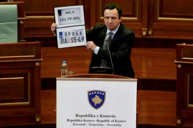 Kosovo Prime Minister Albin Kurti shows Kosovo and Serbia temporary car plates during a parliament session in Pristina on September 20, 2021
