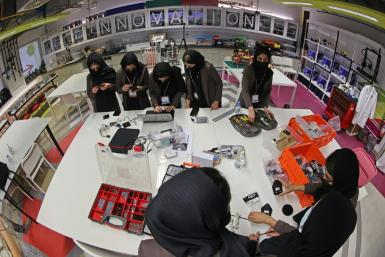 Members of an all-girl Afghan robotics team assemble components for a circuit board they are building, at the laboratory of Qatar's Texas A&M university in the capital Doha