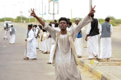 A protester flashes victory signs following the arrival in Port Sudan of a delegation led by a member of Sudan's ruling Sovereign Council on September 26, 2021