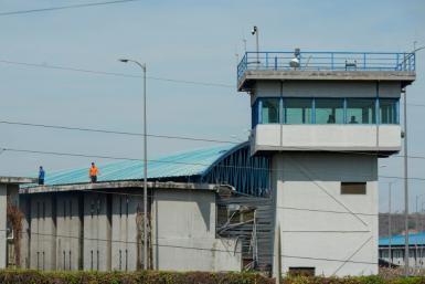 Inmates walk on the roof of a wing of the main regional prison in Guayaquil, Ecuador, where at least 24 prisoners were killed in a gun battle among inmates