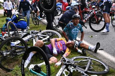 Dozens of Tour de France riders fell after one clipped a sign brandished by a spectator