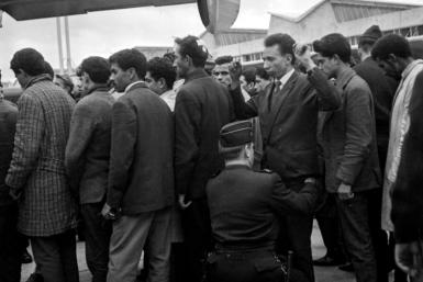 Algerians arrested during the demonstration in Paris on October 17, 1961 are searched before boarding a plane bound for Algeria
