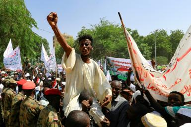 Sudanese protesters take part in a rally demanding the dissolution of the transitional government, outside the presidential palace in Khartoum on Saturday