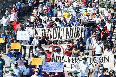 People take part in a demonstration against the circulation of Bitcoin and other economic measures, as well as a decree that removed judges from their functions, in San Salvador, on October 17, 2021