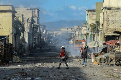 In this file photo taken on December 20, 2019, people walk on a deserted road in Port-au-Prince, Haiti