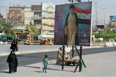 Iraqis pass by a poster of Shiite cleric Muqtada al-Sadr in Sadr City in Baghdad on October 17, 2021
