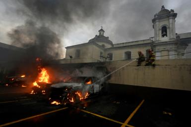 Firemen try to put out a burning car in the parking lot of Guatemala's Congress building, where protesting ex-soldiers clashed with riot police